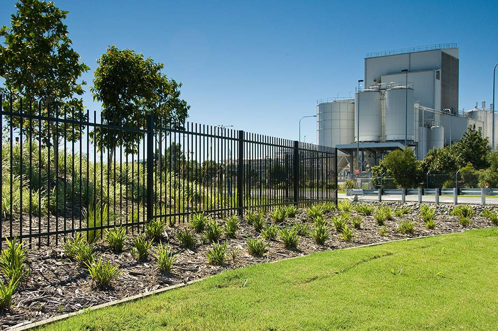 Landscape garden beds and black security fence